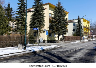 Zakopane, Poland - March 22, 2018: Along the street, in the vicinity of coniferous trees, there are multi-family buildings forming a small housing estate