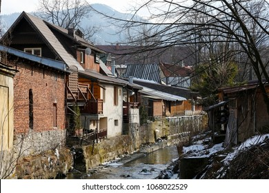 Zakopane, Poland - March 23, 2018: The landscape behind the buildings shows a river flowing through a reinforced concrete riverbed. There are also trees without leaves, because it is winter.