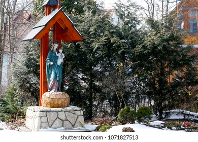Zakopane, Poland - March 23, 2018: Under a small sloping roof stands a statue of Our Lady with the Child Jesus. It is a picturesque little wooden chapel, which can be seen in the winter sun