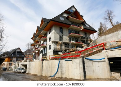 Zakopane, Poland - March 23, 2018: The solid concrete building is already covered by a roof, but still requires a lot of finishing work. This is how a modern hotel building is built