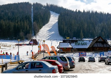 Zakopane, Poland - March 24, 2018: On the slope of the hill of the local name Nosal, among the forest areas there is a snowy ski slope. There is also a car park and a wooden building