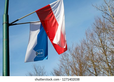 Zakopane, Poland - November 09, 2018: Two flags placed on a mast are waving in the wind. There are white and red flag of Poland together with the blue and white flag with the coat of arms of Zakopane