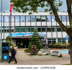 ZAKOPANE, POLAND - SEPTEMBER 29, 2018: City Hall on 29 September 2018 in Zakopane, Poland. In front of the City Hall there is a monument of Andrzej Chramec - a doctor and a social worker from Podhale