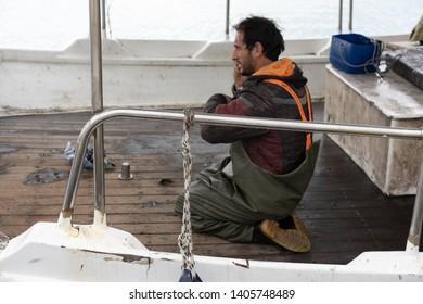 Zakynthos, Greece -  April 2019 : Fisherman talking on a mobile phone on his boat in Zakynthos Port Zakynthos City