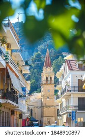 Zakynthos-Greece-July 05, 2013: clock Tower on Zakynthos city street on a clear Sunny day, view through the leaves