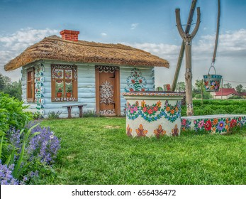 Zalipie, Poland - May 20, 2017: Colourful house with flowers painted on  walls and sundial  in the village of Zalipie in Malopolska, spring time
