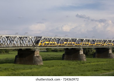 ZALTBOMMEL, THE NETHERLANDS - JULY 24, 2014. Yellow-and-blue intercity train crossing the railway bridge across the floodplains of the river Waal.