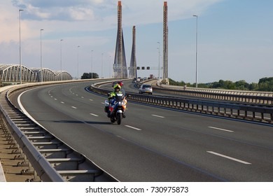 ZALTBOMMEL, THE NETHERLANDS - JULY 24, 2014: A Dutch police man riding a motorcycle across the Martinus Nijhoff bridge near Zaltbommel.