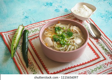 Zama, romanian and moldavian chicken soup with noodle. Traditional hangover soup is served with hot pepper and sour cream.