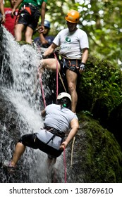 ZAMORA REGION, YANTZAZA, ECUADOR-May 11:Rappel student climbs down waterfall guided by instructors in Yantzaza, Ecuador on May 11, 2013. Rappelling is part of a tourism class.