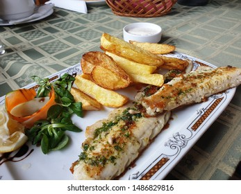 Zander fish fillet and potatos on a table in outdoor restaurant