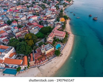 Zanzibar Aerial Shot of Stone Town Beach with Traditional Dhow Fisherman Boats in the Ocean at Sunset Time