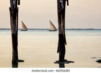 Zanzibar Fishing Boats  Fishing boats, known as dhows, seen through pier pilings as they head for shore off the coast of Zanzibar.