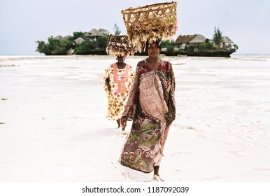Zanzibar, Zanzibar / Tanzania - August 18th 2017: Women Collecting Seaweed At Low Tide On The Island Carry Baskets On Their Heads