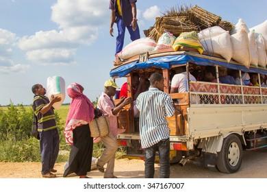 ZANZIBAR, TANZANIA - CIRCA JULY 2013: People loading cargo and luggage on local public transport vehicle known as Daladala, on July 2013. Daladalas are cheap crowded minibuses operating on the island.