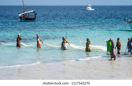 Zanzibar, Tanzania, East Africa - June 23, 2017: African women from a fishing village are catching small fish off the coast of the ocean.