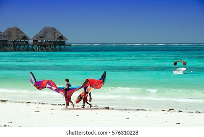 ZANZIBAR, TANZANIA - FEBRUARY 12, 2016: Unidentified men on the white beach with kitesurf, pilework on the background, tropical sea.