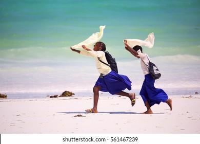ZANZIBAR, TANZANIA - JANUARY 11, 2017: Schoolgirls running home from school along beach in Kiwengwa, Zanzibar Island, Tanzania, Africa