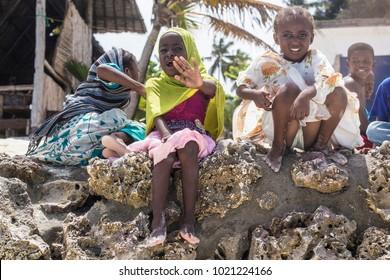 ZANZIBAR, TANZANIA - January 2018: African kids on the beach smiling for camera. Small African girls and boys having fun on the beach, Tanzania