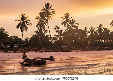 ZANZIBAR, TANZANIA - January 2018: Beautiful sunrise at the sea coast in Kizimkazi, Zanzibar, Tanzania. Silhouette of the fisherman with a boat against orange sunrise sky at Zanzibar, Tanzania