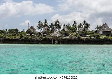 ZANZIBAR, TANZANIA - January 2018: Beautiful Zanzibar coastline with turquoise water. View from the boat on luxury resort at Zanzibar, Tanzania