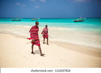 ZANZIBAR, TANZANIA - January 2018: Two Masai friends dressed in traditional clothes walking along the beach, Zanzibar, Tanzania