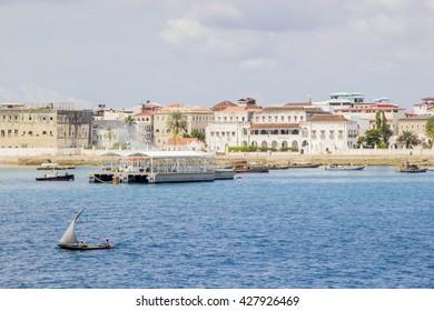 ZANZIBAR, TANZANIA - JUNE 16: small vessel sailing along the coast near a pier outside Stone Town on June 16, 2013 in Zanzibar. Stone town is the former capital of the Zanzibar Sultanate