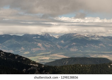 Zapadne Tatry mountain range from Kralov stol bellow Dumbier peak in Nizke Tatry mountains in Slovakia uring autumn day with blue sky and clouds