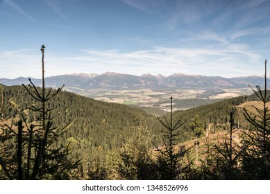 Zapadne Tatry and wetsrnmost part of Vysoke Tatry mountain range from hiking trail bellow Slema hill in Nizke Tatry mountains in Slovakia during beautiful autumn day