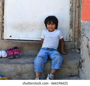 ZAPOPAN, JALISCO,  MEXICO, OCTOBER 10, 2012 MEXICAN BOY SITTING OUTSIDE OF THE FRONT Of HIS HOUSE
