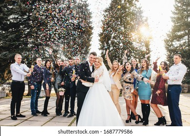 Zaporizhia, Ukraine - February 29, 2020. Full-size portrait of newlyweds and their friends at a wedding party showered with confetti in a green sunny park
