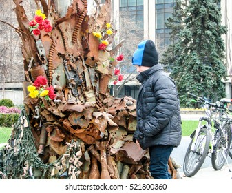 """ZAPORIZHIA, UKRAINE - NOV 18 2016: Child sees the sculpture """"Iron throne of East Ukraine"""" made from used weapons and created around area of conflict between Russia and Ukraine in Donetsk and Lugansk."""