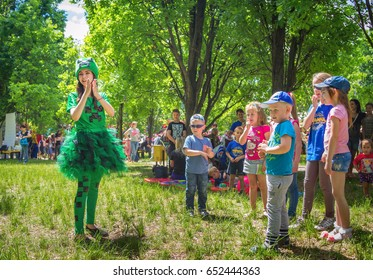 Zaporizhia/Ukraine- May 28, 2017: Charity Family festival – children playing with entertainer – young woman in a funny green costume