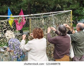 Zaporizhzhia / Ukraine - SEP 16, 2018: volunteers weave a camouflage net for the Ukrainian army - the flag of the city of Zaporozhye (Zaporizhia) and of Ukraine in the background.