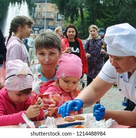 """Zaporizhzhia / Ukraine - SEP 16, 2018: Happy and enthusiastic children at the culinary master class during a massive public event (""""All-Ukrainian Festival of Homemade Canning"""") - city of Zaporozhye."""
