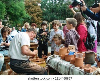 """Zaporizhzhia / Ukraine - SEP 16, 2018: enthusiastic children at the pottery master class during a massive public event (""""All-Ukrainian Festival of Homemade Canning"""") - city of Zaporozhye."""