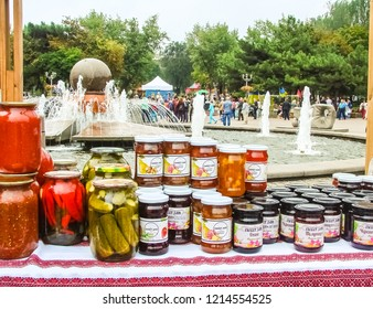 "Zaporizhzhia / Ukraine - SEP 16, 2018: Homemade canning (pickles, jam, marmalade, confiture) of the ""All-Ukrainian Festival of Homemade Canning"". Fountain and people activities in the background."