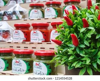 "Zaporizhzhia / Ukraine - SEP 16, 2018: Homemade canning (inscription on jars ""seasoning adjika green"" in ukrainian) of the ""All-Ukrainian Festival of Homemade Canning"" in the city of Zaporozhye."