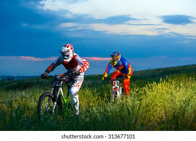 ZAPORIZHZHYA, UKRAINE - JUNE 16, 2015: Two Fully Equipped Professional Downhill Cyclists Riding Bikes on the Summer Trail. Extreme Sports