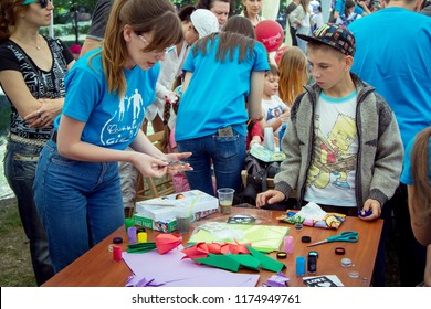 Zaporozhia/Ukraine- June 2, 2018: Charity Family festival-young woman – volunteer explaining to teen boy how make colorful paper tulip flowers at art and craft workshop, outdoors children activity