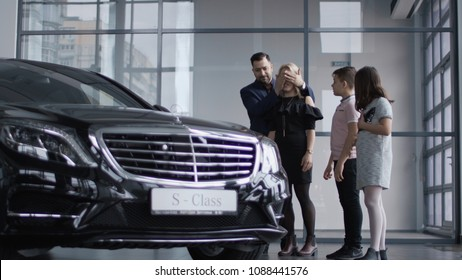 ZAPOROZHYE, UKRAINE - APRIL 3, 2018: The successful husband made a gift to his wife and gave her a Mercedes Benz car, the woman is very emotional and surprised and they hug themselves together near