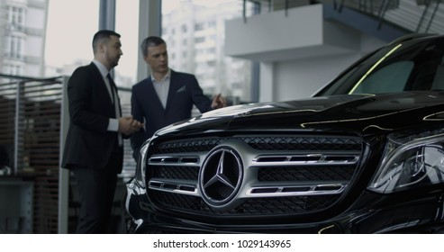 ZAPOROZHYE, UKRAINE, JANUARY 18, 2018: Elegant salesman presenting new Mercedes Benz car to potential buyer in showroom