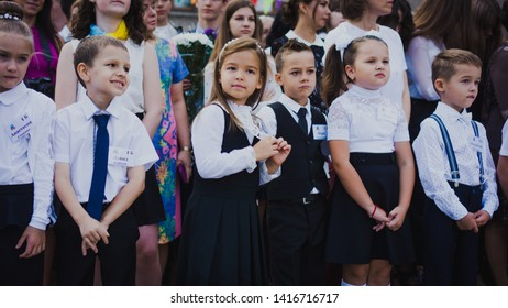 Zaporozhye, Ukraine - September 1, 2018: first-graders stand on a ruler in the open air with teachers and high school students on the ceremonial school line on the day of knowledge. Close-up.