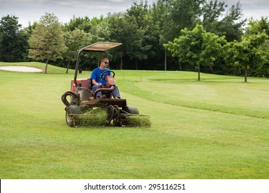 ZAPRESIC, CROATIA - JULY 09, 2015: Golf course worker mows the grass of a green in the early morning on a Novi Dvori golf course