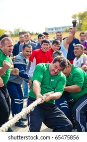 """ZARAFSHAN, UZBEKISTAN - OCT. 30:  Traditional tug of war competitions dedicated to the professional holiday """"Avtomobilist Day"""". Motorists are competing October 30, 2010 in Zarafshan, Uzbekistan."""