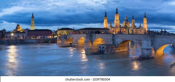 Zaragoza - The panorama with the bridge Puente de Piedra and Basilica del Pilar at dusk.