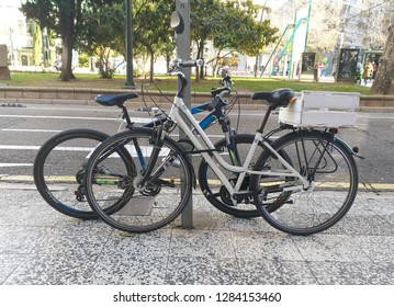 ZARAGOZA, SPAIN ; 01 14 2018 : TWO BYCICLES LOCKED BY PADLOCKS TO A TRAFFIC SIGNAL IN THE URBAN SIDEWALK OF A STREET WHILE BEHIND THE SCENE A RIDER CYCLES OTHER BYCICLE ON THE ROAD.