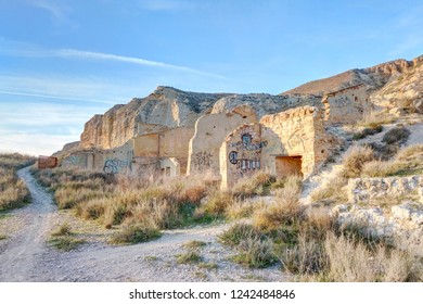 Zaragoza, Spain - March 02, 2017: An abandoned rumbled building with some graffiti next to a scarp during a winter sunset in Galacho del Juslibol rural area, Zaragoza, Aragon, Spain