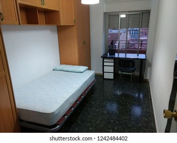 Zaragoza, Spain - May 27, 2018: An empty flat room with a bed, bridge wardrobe, a black and white desk, a chair and dark floor in Zaragoza, Spain