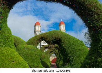 Zarcero church tower seen through one of its ornamental garden arches